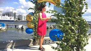 I blåsten under den lövade  bågen och ballongerna  invigde kommunalrådet Carin Lidman (S) den nygamla stenpiren.