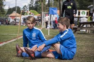 Sixten Hågerstam åtta år och Herman Schedin nio år sitter i gräset och tittar på fotboll. Killarna berättar att de vann sin första match med 9-4.