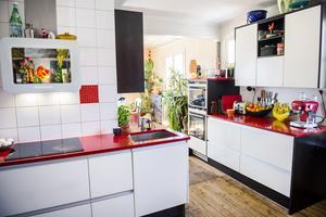Köket är färgstarkt med röda bänkskivor och svarta och vita detaljer.