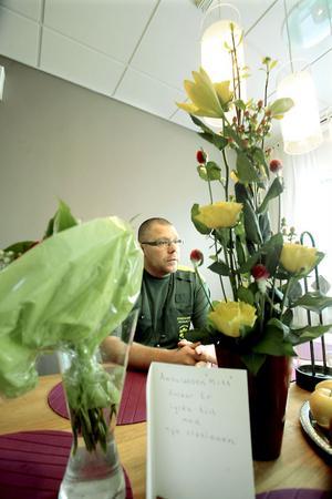 Micke Ericsson, enhetschefen på ambulansstationen i Hudiksvall och blommor från invigningen.