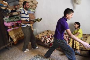 Pappa Mahmoud får hjälp att bädda av barnen Bayan 12 år och Muhammed 16 år i ett av husets två rum.
