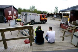 Utanför butiken satt en chockad kund, och väntade på ambulans. Tidigare hade två personer förts till sjukhuset.