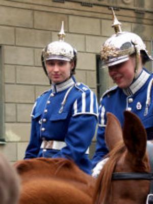 Ulrika Mossberg till häst bredvid en kollega. Prydnaden på hjälmen kallas pickel. I riktigt högtidliga sammanhang bär soldaterna plym i stället.