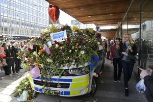 En polisbil täckt av blommor vid Sergels Torg i Stockholm efter terrordådet på Drottninggatan.