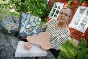 Kersin Hörnlund med modellen av sittskulpturen och ett prov på mosaiken. I verkstaden pågår arbetet med skulpturen i full skala.