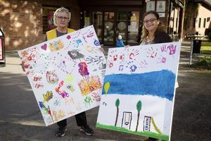 Anki Rooslien och Erika Jernberg med två av de fyra aktuella tavlorna, pengarna de drar in går till Världens Barn.