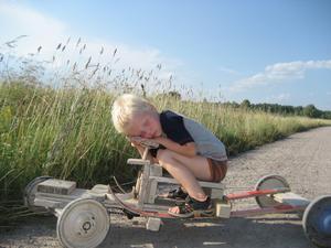"""I somras när jag och mitt barnbarn Natanael 3,5 år var på tur med min """"lådbil"""" somnade han vid ratten. Jag märkte att det gick mot dikeskanten och när vi stannade vek Natanael ihop sig över ratten och somnade. (Lådibilen tillverkad av mig 1960 av min slaktade barnvagn årsmodell 46. Lådbilen morderniserad med ny fjädring bestående av ett par skidor. Tidigare fjädring var enestörar.)"""
