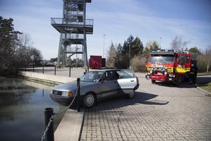 Två personer är skadade och bilen måste säkras så att den inte åker över kajkanten.