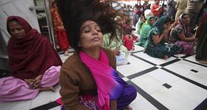 En kvinna rullar på huvudet i trance, i ett Kalitempel, i Jammu, Indien.