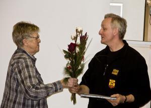 Kultur- och samhällsutvecklingsnämndens ordförande Lillemor Svensson ger stipendiat Sven-Ulrich Olsson en blomsterkvast och diplom.