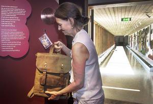 Ann-Sofie Axelsson med en tung dåtidens plånbok med en stor kopparslant i samt moderna tiders plånbok med ett betalkort som hänger på väggen.