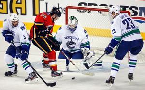 Eddie Läck räddar ett skott från Calgary Flames Ben Street under andra perioden. Till höger övervakar svenske backen Alexander Edler och till vänster Jason Garrison.