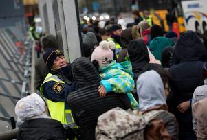 En polis försöker muntra upp en liten flicka i kön av ankommande flyktingar på Hyllie station i november 2015, när strömmen av asylsökande till Sverige var som störst. Foto: Johan Nilsson/TT