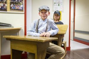 Femteklassarna Tristan Forsmark Bjöörn och Kalle Blomqvist provsatt de gamla skolbänkarna som lärare funnit på vinden.