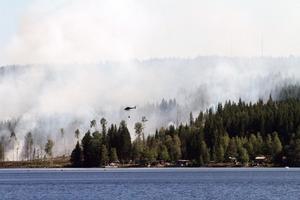 En boende på andra sidan Kastaviken, Jan-Olov Schröder, tog en bild på helikoptern som vattenbombade branden under eftermiddagen. Vattnet hämtades från den närliggande viken.Foto: Jan-Olov Schröder