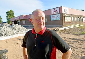 Handlaren framför sin butik. Till vänster om honom anläggs en ny parkeringsplats och byggnadens vänstra del ska byggas ut med bland annat en ny entré samt spel- och postrum.