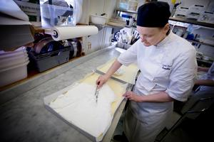 Camilla Nuikka brer ut marängsmeten ovanpå sockerkassmeten. Därefter ska den gräddas i 45 minuter.