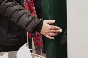 Den vita knappen på baksidan av maskinen med kölappar signalerar till apotekspersonalen att en synskadad vill ha hjälp.