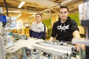 Felix Otzheino och Rasmus Persson sitter vid en rad med vagnar som ska förbindas i en automationskedja. Varje elev har sin egen vagn och det blir en grupputmaning att få det hela att fungera. Än har de inte nått hela vägen fram med uppgiften.
