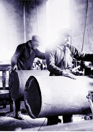 Erik Karlsson och Hilmer Karlsson tillverkar oljefat av tunn metallplåt, troligtvis under 1950-talet.