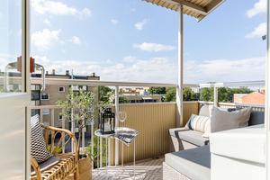 En mindre balkong i centrala Gävle som Therese har inrett med en liten loungehörna, ett brickbord och en rottingfåtölj. Foto: Alexander Lindström