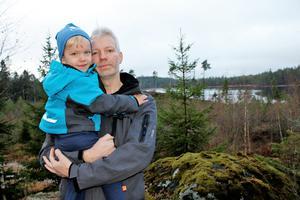 Mattias Almsin, här med sonen Måns, 3 år, är nyfiken på vem som kan ha gjort hällristningen. Fyndplatsen ligger på en höjd bara några stenkast från sjön Orkaren (i bakgrunden).