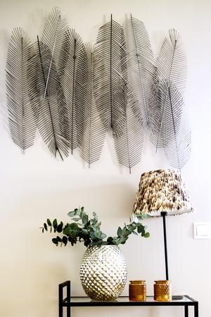 Fjädertavlan skapar spännande skuggor mot den ljusa väggen.