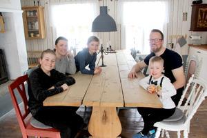 Familjen Olén vid köksbordet som de tillverkat av gamla golvplankor.
