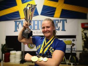 Ida Rönn med pokalen för bästa damjuniorlyftare under VM, guldmedaljen för totalsegern samt två för individuella disciplinsegrar också. FOTO: FYSHUSET
