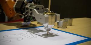 Här ritar roboten i konturer med en penna. Den har fått förprogrammerade punkter så roboten känner av var linjerna ska ritas in.