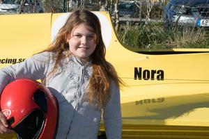 Nora Jansson poserar stolt framför sin illgula racerbåt som hon kommer tävla med 1 juni.