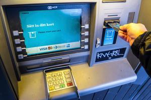 En kund tar ut pengar i bankomaten.
