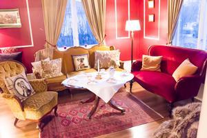 I det röda rummet brukar gästerna få dricka kaffe och whisky. Möblerna som Madeleine inreder med hittar hon på auktioner och loppisar.