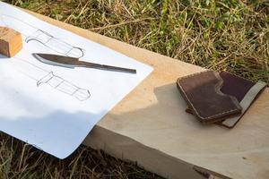 Återbruk är en ledstjärna i Mikael Ahlqvists arbete. På pappret syns en skiss till ett knivskaft, där alla delar är i trä som blivit över från andra projekt. Knivämnet är utskuret ur en rostig sågklinga. Korthållarna har han sytt av spillbitar av läder som blivit över efter att ha gjort knivslidor.