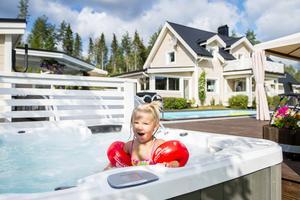 Spabadet har sänkts ner i ett hörn av altanen. Barnbarnet Elvira trivs – som fisken i vattnet.