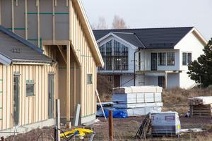 Flera tomter är ännu obyggda. Men majoriteten av de sålda – sju av totalt åtta – har fått bygglov. Här är två av husen som hittills rests på platsen. Ett nästintill färdigt – och ett under byggnation.