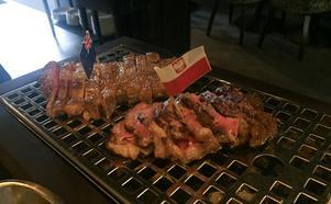 En liten flagga följde med köttet in på bordet. Krogpatrullen valde ryggbiff från Nya Zeeland och polsk picanha. Köttet serveras uppskuret på het platta med en glödbädd i ena hörnet.
