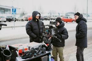 SVT:s team filmar en kort sekvens där en taxi, med två Västeråsstatister i, åker i väg. Längst till vänster står regissör Simon Kaijser. Foto: Martin Bohm