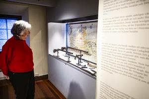 Elisabeth Breig Åsberg i museets utställning om gevären som tillverkades i Söderhamn. Till höger finns delar från texten i privilegiebrevet som Gustav II Adolf utfärdade, när Söderhamn blev en stad 1620.