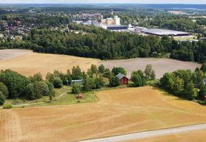 Debattörerna skriver att det snart kan finnas 45 odlingslotter på  fältet framför det gamla magasinet på Mora gård . I bakgrunden syns Moraån och längre bort Järna samhälle. Foto: Privat