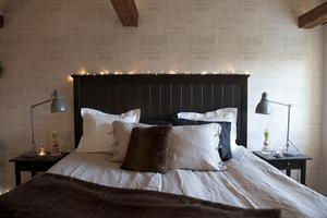 Den mörka sänggaveln bryter av mot den skira tapeten med snirklig handstil från 1800-talet.