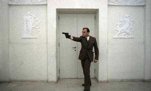 Överklassbyråkraten Marcello Clerici (Jean-Louise Trintignant) visar upp sina färdigheter med pistol i Bernardo Bertoluccis film