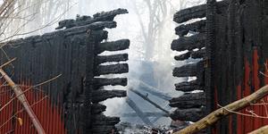 De gamla trästockarna bakom den nyare träpanelen är alldeles svartbrända och visar hur branden slukat det gamla huset utmed Kolbäcksån.
