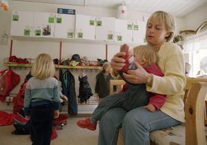 Ett förskolebarn får hjälp att ta på sig skorna inför uteleken på en förskola. Det är många behov som behöver uppfyllas av personalen. Foto: Erik G Svensson/TT