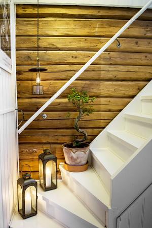 Den vita trappen blir en fin kontrast mot de timrade väggarna.