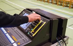 Mixar ljudet på genrepet till Scheeleskolans avslutning i deras idrottshall.