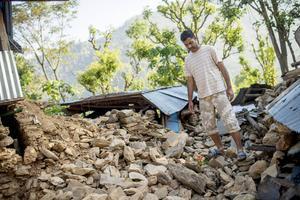 Ram Sapkota går igenom vad som tidigare var hans familjs hus och ägodelar. Foto: Jonas Gratzer
