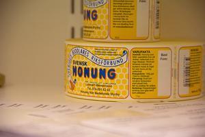 Lennart Wernersson har egna etiketter som han sätter på sina burkar med nyslungad honung.