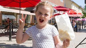 Sarah Horic, 4, är glad över sin popcornpåse. Under dagen har hon tillsammans med föräldrarna besökt tivolit i Vilhelminaparken och åkt tåg, åkt flygplan och hoppat i hoppborgen.