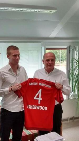 Thomas Isherwood håller stolt upp Bayern München-tröjan med sitt namn på ryggen. Tillsammans står han med en till synes mycket nöjd